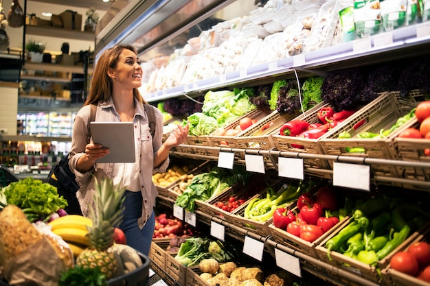 Vrouw die met tablet gezond voedsel in supermarkt-kruidenierswinkelopslag kopen