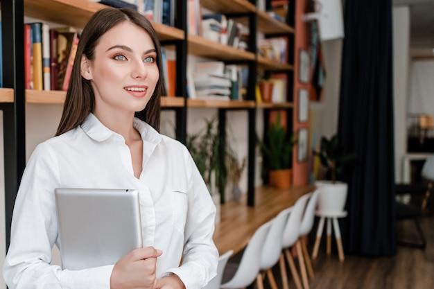 Vrouw die met tablet in het bureau glimlacht