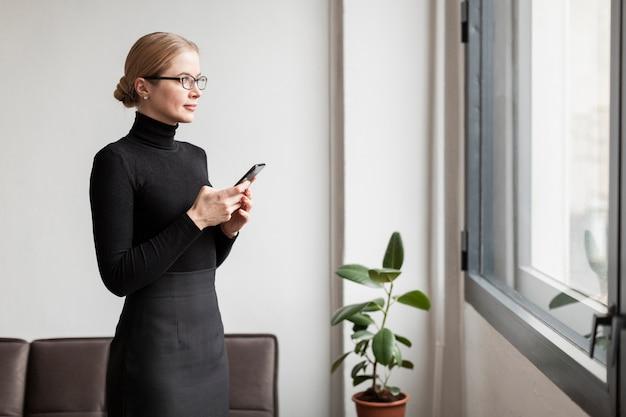 Vrouw die met telefoon op venster kijkt