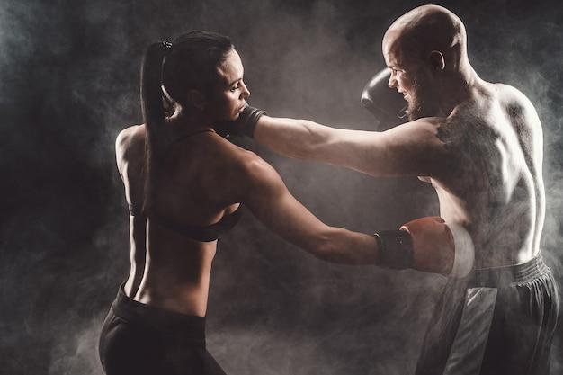 Vrouw die met trainer bij boksen en zelfverdedigingsles uitoefent vrouwelijke en mannelijke strijd
