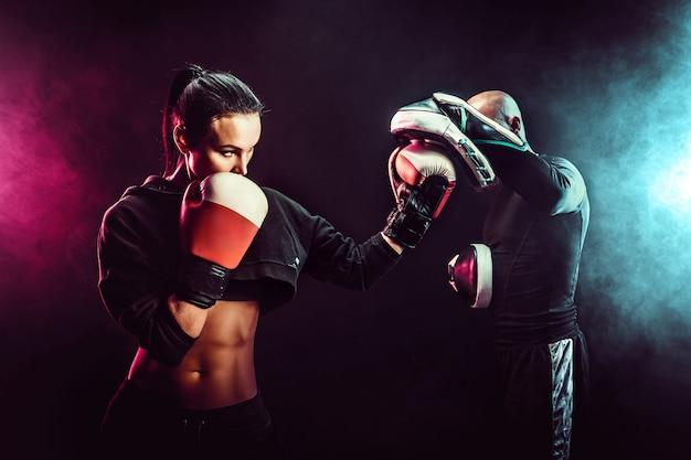 Vrouw die met trainer bij het in dozen doen en zelfverdedigingsles uitoefenen
