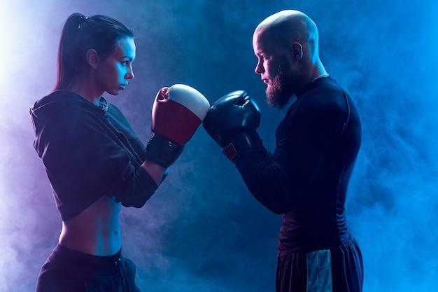 Vrouw die met trainer bij het in dozen doen en zelfverdedigingsles uitoefent kijkt agressief elkaar. ga vooraan staan.