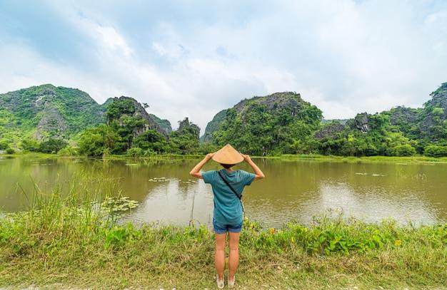 Vrouw die met vietnamese hoed unieke mening van tam coc trang een de toeristenbestemming van ninh binh bekijken in vietnam
