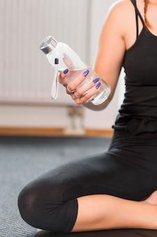 Vrouw die met violette spijkers fles water houdt