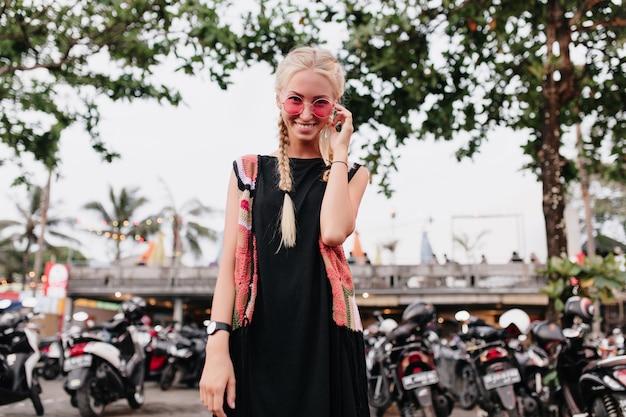 Vrouw die met vlechten door roze zonnebril kijkt. emotionele blonde dame in zwarte jurk die zich voordeed op straat achtergrond wazig.