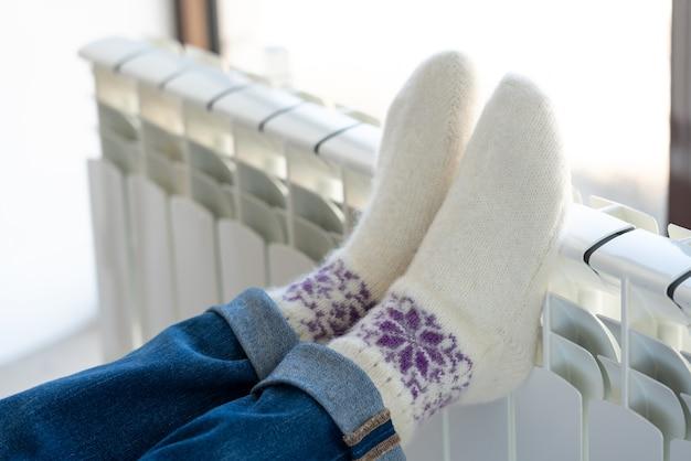 Vrouw die met voeten op verwarmer opwarmen die wollen sokken dragen
