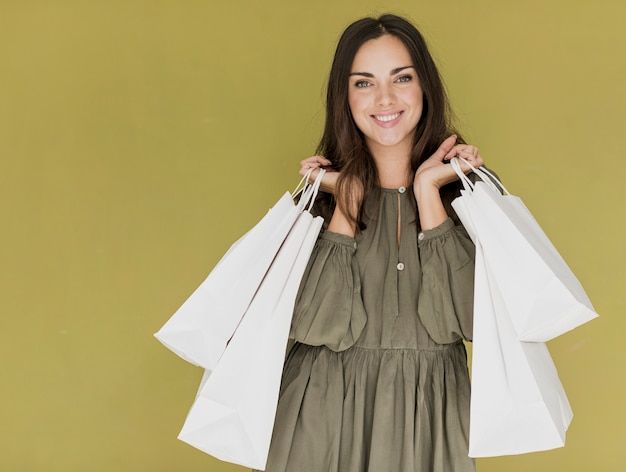 Vrouw die met winkelnetten in beide handen aan de camera glimlacht