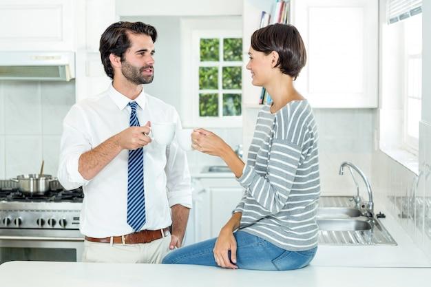 Vrouw die met zakenman tijdens koffiepauze interactie aangaan