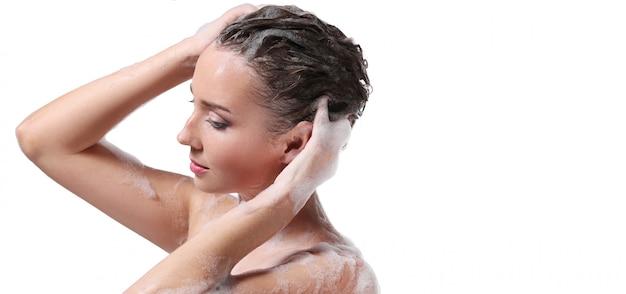Vrouw die met zeep op het lichaam en het hoofd overgiet. hygiëne en huidverzorging concept