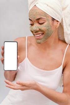 Vrouw die met zelfgemaakt gezichtsmasker een lege smartphone houdt