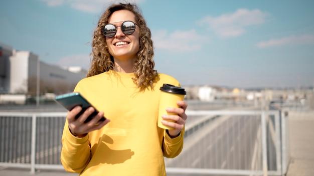 Vrouw die met zonnebril een kop van koffie houdt