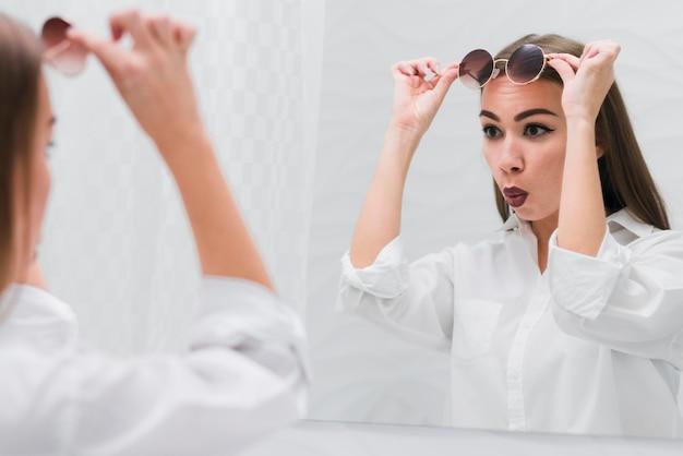 Vrouw die met zonnebril in de spiegel kijkt