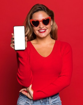 Vrouw die met zonnebril smartphone houdt