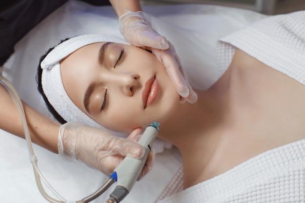 Vrouw die microdermabrasie therapie op voorhoofd ontvangt in beauty spa