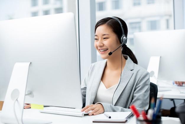 Vrouw die microfoonhoofdtelefoon draagt die in call centrebureau werkt