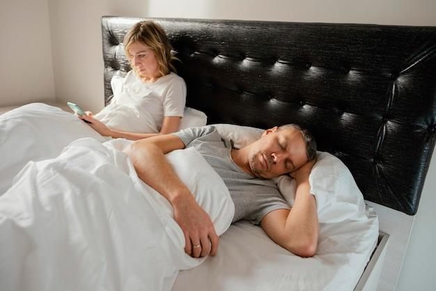 Vrouw die mobiel gebruikt terwijl echtgenoot slaapt