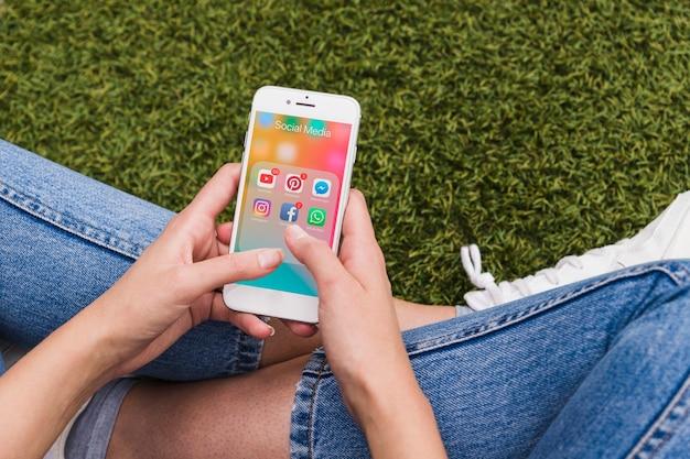 Vrouw die mobiel houdt gebruikend sociale netwerktoepassingen