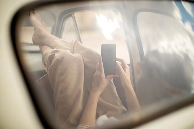 Vrouw die mobiele telefoon binnen retro auto bekijkt