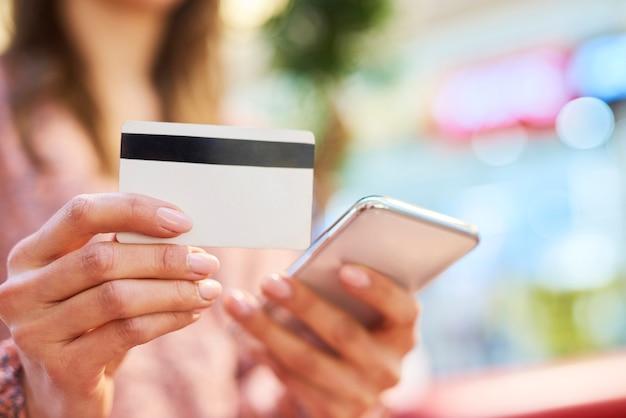 Vrouw die mobiele telefoon en creditcard gebruikt tijdens online winkelen