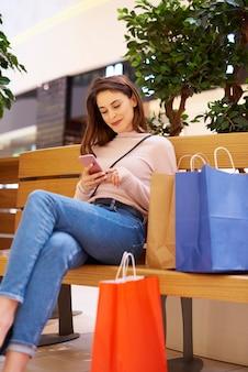 Vrouw die mobiele telefoon gebruikt na groot winkelen in winkelcentrum