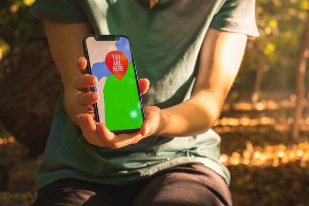 Vrouw die mobiele telefoon gebruikt voor navigatie in het bos. scherm met kaarten en je bent hier teken