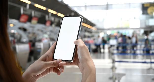 Vrouw die mobiele telefoon in eindluchthaven met behulp van