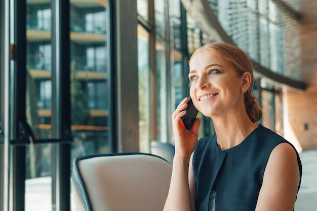 Vrouw die mobiele telefoon in het bureau met behulp van