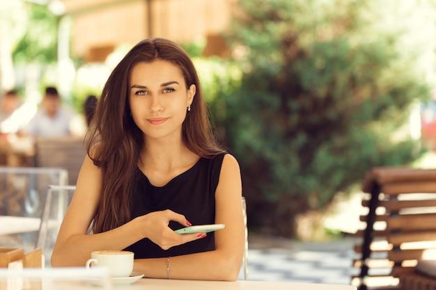 Vrouw die mobiele telefoon in koffie met behulp van