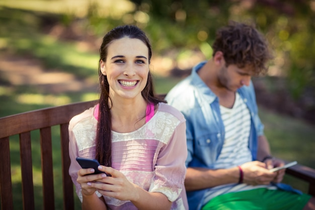 Vrouw die mobiele telefoon in park met behulp van
