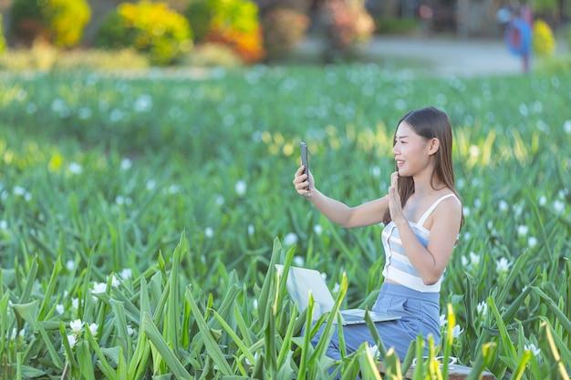 Vrouw die mobiele telefoon met behulp van om foto in de bloementuin te maken.