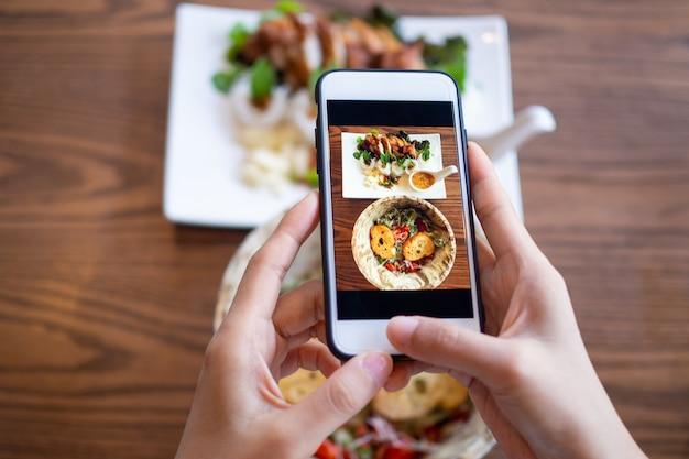 Vrouw die mobiele telefoon met behulp van om foto's van voedsel op de lijst te nemen. op mobiel genomen en op sociale netwerken gezet.