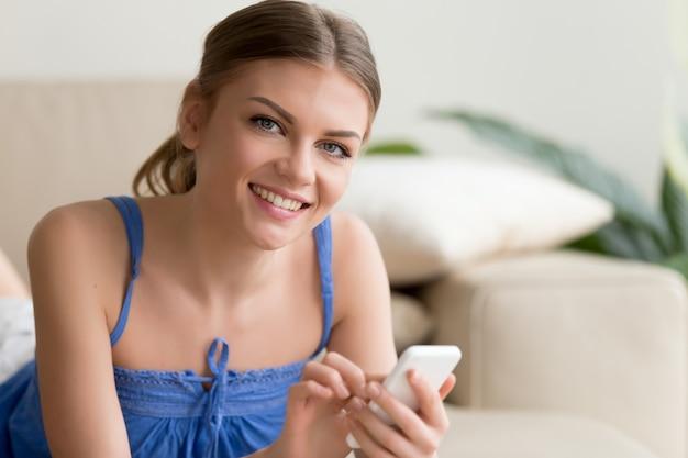 Vrouw die mobiele telefoon met behulp van terwijl thuis het rusten
