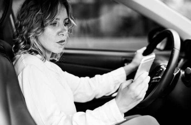 Vrouw die mobiele telefoon met behulp van tijdens het rijden