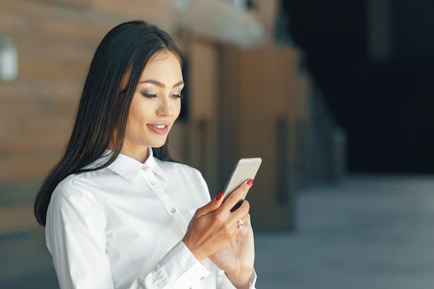 Vrouw die mobiele telefoon op het kantoor met behulp van