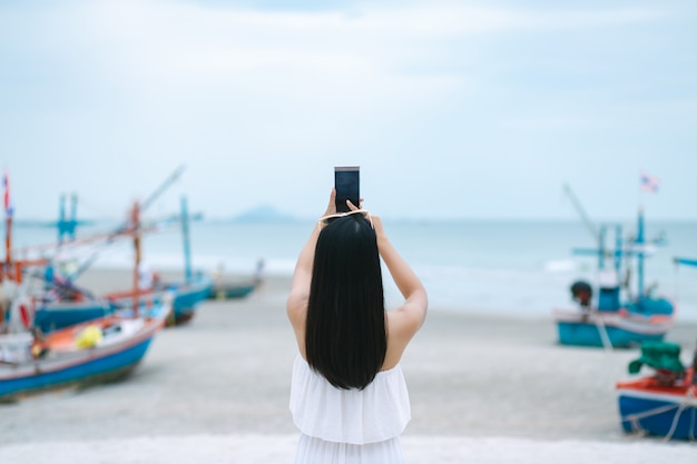 Vrouw die mobiele telefoon op strand met behulp van
