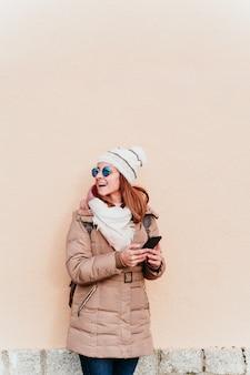 Vrouw die mobiele telefoon over gele muur met behulp van. technologie en winter concept