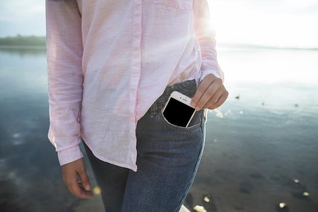 Vrouw die mobiele telefoon uit de zak verwijdert