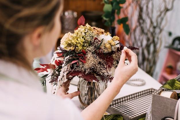Vrouw die mooie bloemenregeling maakt