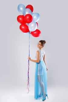 Vrouw die mooie jurk met veel kleurrijke ballonnen draagt