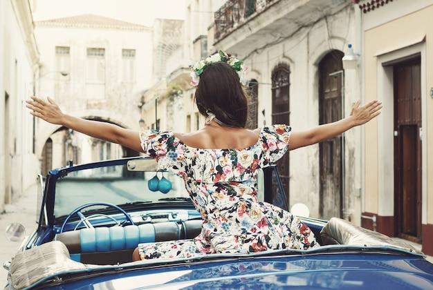 Vrouw die mooie kleding en retro converteerbare auto draagt bij de stad van havana
