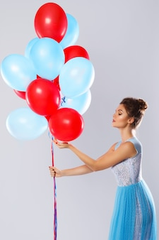 Vrouw die mooie kleding met heel wat kleurrijke ballons draagt