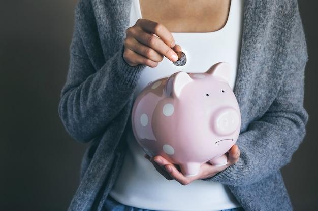 Vrouw die munten in een droevig spaarvarken stopt vrouw spaart geld voor huishoudelijke betalingen bankbiljetten