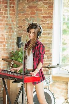 Vrouw die muziek opneemt terwijl ze zingt en piano speelt terwijl ze op zolder of thuis staat