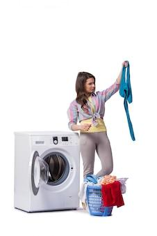 Vrouw die na het doen van wasserij wordt vermoeid op wit wordt geïsoleerd