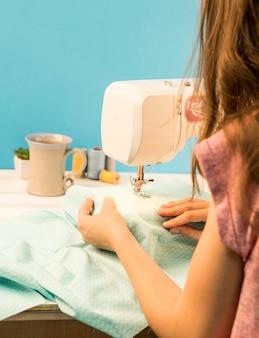 Vrouw die naaimachine met behulp van
