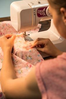 Vrouw die naaimachine op bloemrijk patroon met behulp van