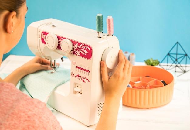 Vrouw die naaimachine op groene stof met behulp van
