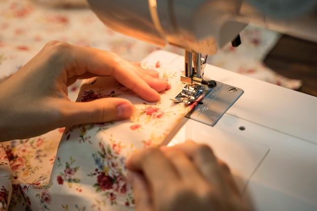 Vrouw die naaimachine op materiaal met behulp van