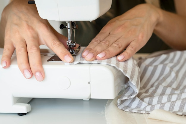 Vrouw die naaimachine op textiel met behulp van