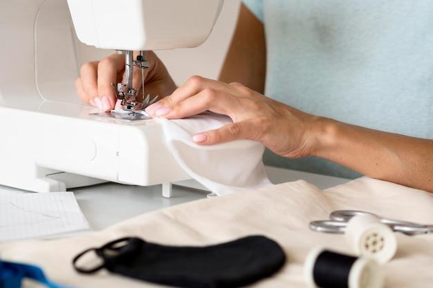 Vrouw die naaimachine voor gezichtsmasker gebruikt